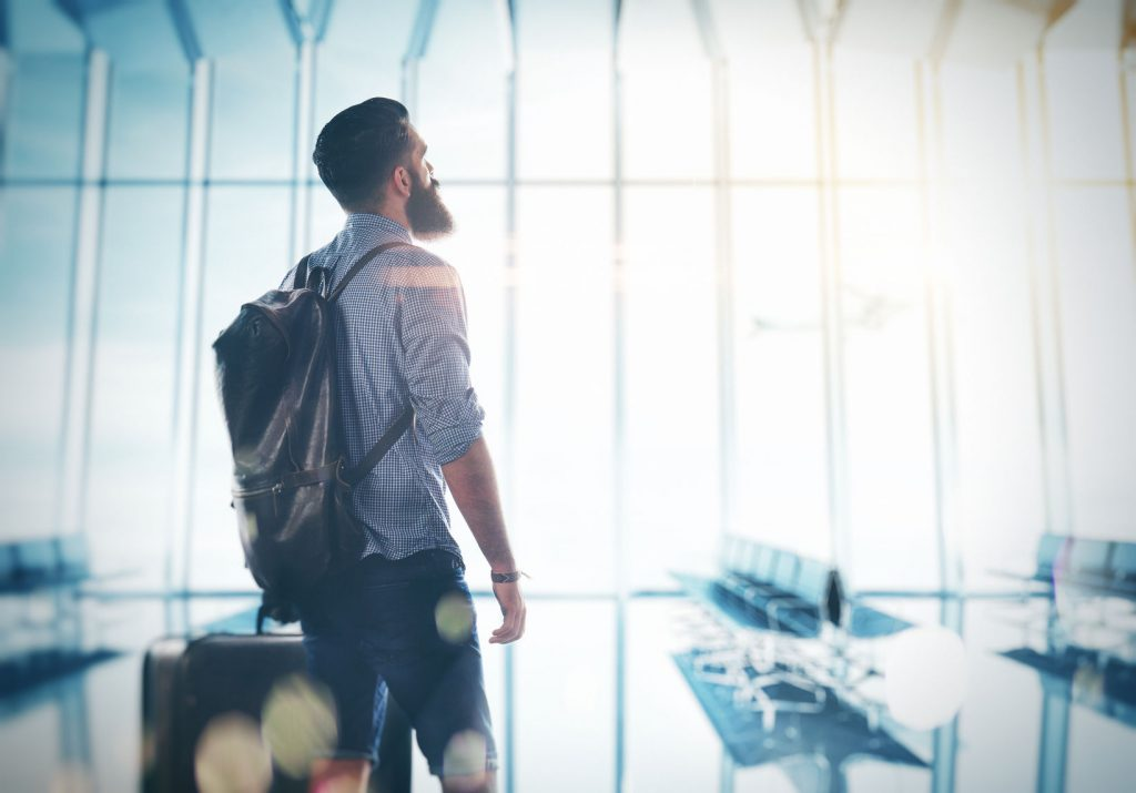 Bearded man standing at the airport with a suitcase and backpack